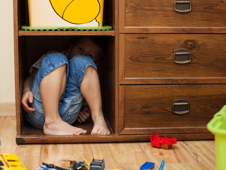 cruelty: abuse and cruelty to children - little boy is hiding in a cupboard in the room