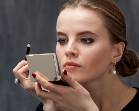 Young woman applying makeup on the eye with eyeliner