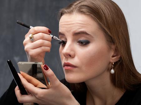 Giovane donna applicare il trucco sull'occhio con eyeliner