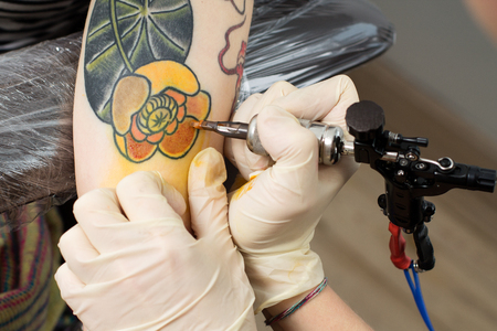 Tattoo process - masters hands with tattoo machine  making thrift-box flover on the arm Stock Photo