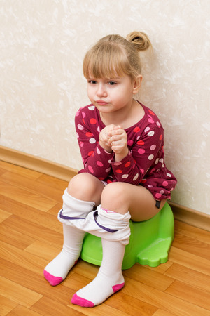 Little girl is sitting on the green childrens potty, loose tights
