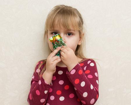 gir: Little gir in a bright dress  eating a candy Stock Photo