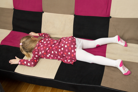 one child: Upbringing problems - little sad girl is lieing on the sofa facedown