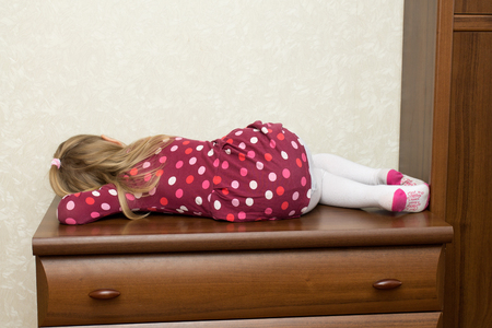 one child: Little girl lies on the chest of drawers facing the wall Stock Photo