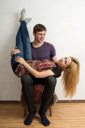 cabeza abajo: Una pareja est� sentada en la silla, la mujer est� acostada boca abajo sobre las rodillas del hombre