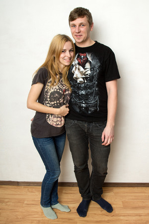 twosome: Young couple in black shirts with prints and jeans smiling against the  white wall, the man is hugging the woman Stock Photo