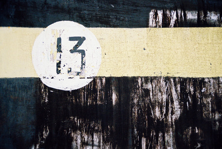 thirteen: Absrtact background - yellow stripe and number thirteen in white circle on black shabby  background Stock Photo