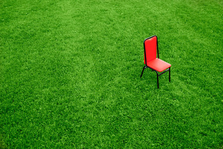 Contrast- one red chair on green grass background Stock Photo