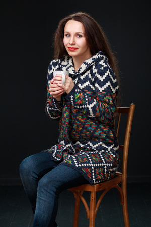 hair wrapped up: Attractive young brunette woman in a sweater sits on a chair and holding a cup of tea in her hands. A girl huddled against the cold. The image on dark background. Stock Photo