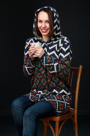 hair wrapped up: Attractive brunette girl in a sweater with a hood holds a mug of tea in the hands sitting in a chair and smiling broadly, on a dark background. Stock Photo