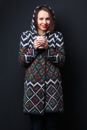 hair wrapped up: Girl in a bright sweater with a hood keeping a cup on dark gray background Stock Photo