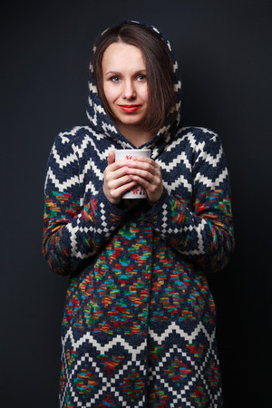hair wrapped up: Woman in a bright sweater with a hood keeping a cup on dark gray background Stock Photo