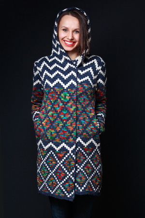 broadly: Young attractive woman in a sweater with a hood smiling broadly into the frame on a black background Stock Photo