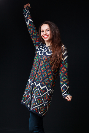 boldness: Emotions, expressions. Young brunette woman in bright sweater smiling, one hand is up, the other is down, boldness, courage. Dark gray background