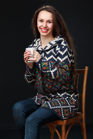 broadly: Attractive brunette woman with a cup of tea sitting on a chair  broadly smiling, on a dark background. Stock Photo
