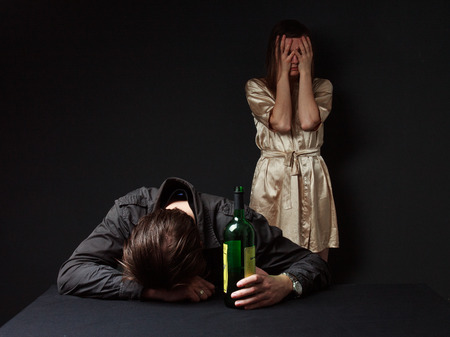 Alcoholism. Drunk man is sleeping on the table with the bottle in the hand, his wife closed face  by the hands , she is in despair Stock Photo