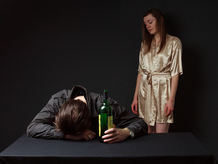 Alcoholism. Drunk man is sleeping on the table with the bottle in the hand, his wife standing behind , she is in despair