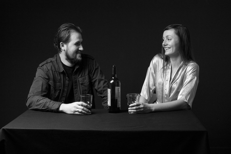 degradation: Alcoholism. Man and woman are drinking alcohol, bottle on the table, smiling. Black and white