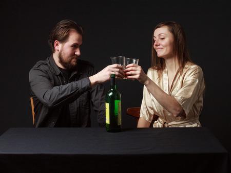 alcoholismo: Alcoholismo. El hombre y la mujer están borracheras, botella sobre la mesa, manteniendo gafas, sonriendo. Foto de archivo
