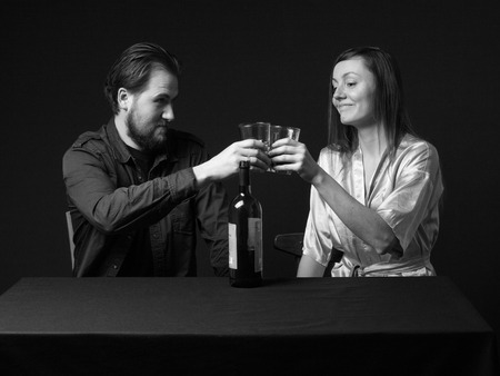 Alcoholism. Man and woman are boozing, bottle on the table, keeping glasses, smiling. Black and white Stock Photo