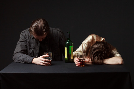 seeping: Alcoholism. Abused couple. Drunk couple, man and woman are seeping on the table, steel keeping glasses.