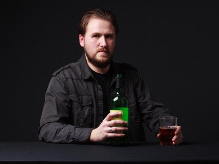 alcoholismo: Alcoholismo. El hombre joven está manteniendo una botella y una copa de vino, fondo gris
