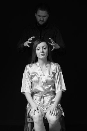 threaten: Violence. Sad woman is sitting on the chair, mans figure  behind threaten her, gray background, black and white image. Stock Photo