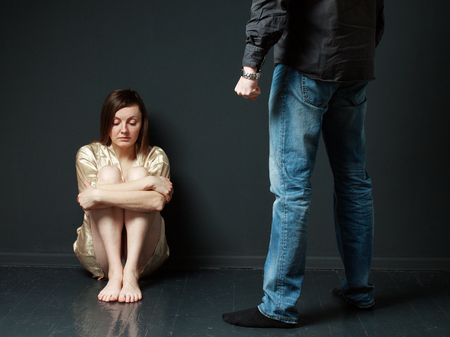 abused women: Domestic violence. Sad woman is sitting on the floor, standing mans figure  threaten her, gray background Stock Photo