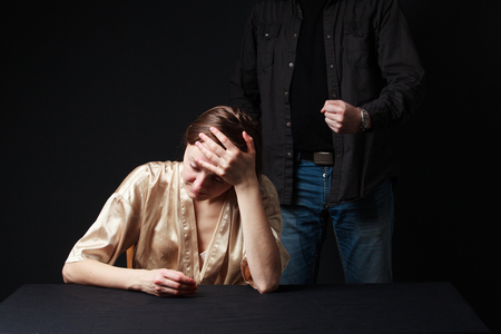 threaten: Abuse. Sad woman is sitting , keeping hand on the forehead, mans figure  behind threaten her . gray background