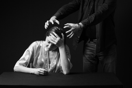 threaten: Domestic violence. Sad woman is sitting , keeping hand on the forehead, mans figure  behind threaten her . gray background