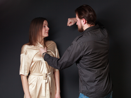 threaten: Abuse. Family fight. Husband threaten wife, he is going to fist her, gray background Stock Photo
