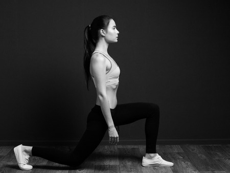 lunge: Exercise and fitness - sports woman doing squat (lunge forward). Black and white image on a black background.