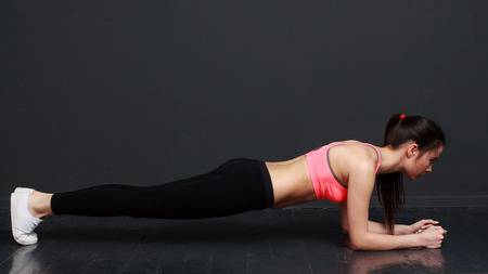 Fitness and motivation - slim athletic woman doing the planck. The image on a black background. Archivio Fotografico