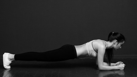 planck: Fitness and motivation - slim athletic woman doing the planck. Black and white image on a black background.