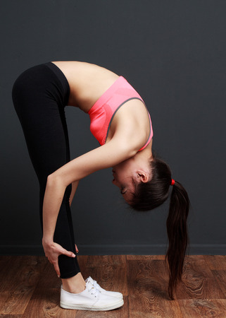 inclination: Exercise and stretching - Fitness woman doing inclination to socks. Model in pink top standing on the floor on a dark gray background. Stock Photo