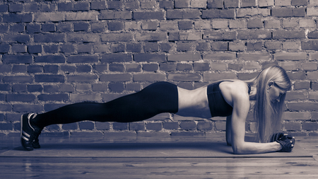 fitness, sport, training and lifestyle concept - woman doing plank exercises on mat at the gym. Toned black and white image.