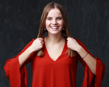 Smiling woman in red dress with a funny hairdo - two tails, gray background Stock Photo