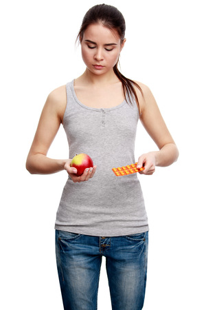 choise: Choise. Young serious woman holding a pill in one hand and an apple in the other, isolated on white background