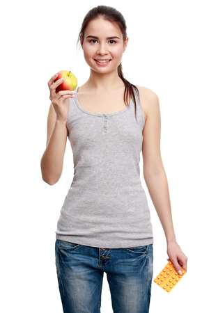 choise: Choise. Young smiling woman holding a pill in one hand and an apple in the other, isolated on white background