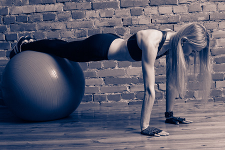 fitball: Attractive blond fitness model performing push ups with a fitball at the gym