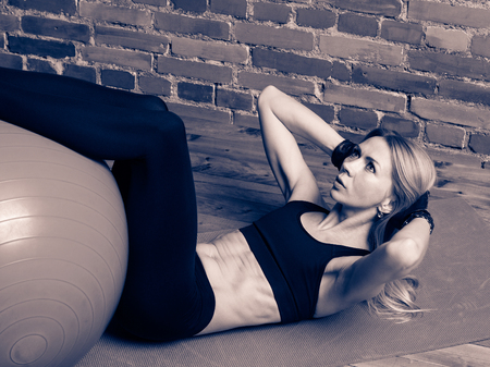 fit ball: Attractive blond fitness woman performing abdominal exercises with a fit ball at the gym