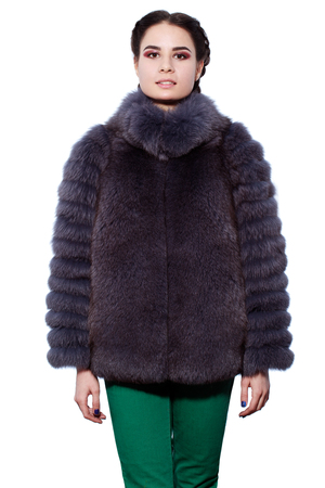 woman in fur coat: Fashion. Young brunette woman in a violet fur coat made of arctic fox and green pants isolated on white background