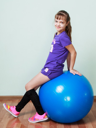 fit ball: Little girl in violet sports costume is sitting on a blue fit ball at the gym, smiling