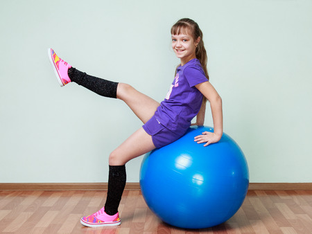 fit ball: Little girl in violet sports costume is sitting on a blue fit ball, lifting the leg, smiling