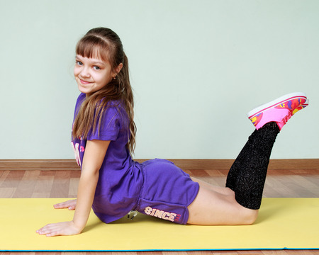 deflection: Children activity. Sports and fitness. Cute girl  in violet sports costume is bending at the waist, doing workout for back and spine