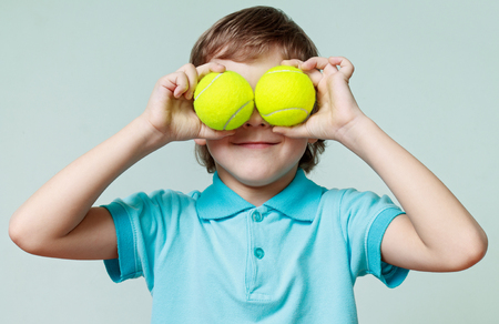Children. Little boy holding tennis balls instead of the eyes, smiling