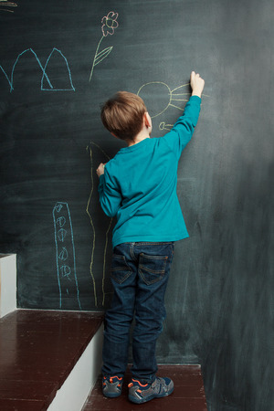 Children activity. Little boy is drawing on a blackdoard, view from the back Stock Photo