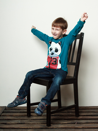 hooray: Children. Little funny  boy is sitting on the chair, hands up, smiling, hooray gestures