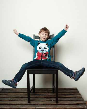 piddle: Children. Little funny  boy is sitting on the chair, piddling, fooling Stock Photo