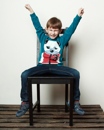 hooray: Children. Little funny  boy is sitting on the chair, hands up, eyes are closed, hooray gestures